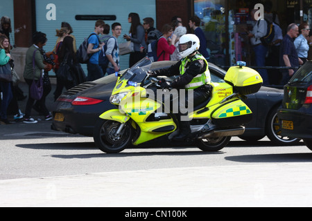 a London ambulance motorcyclist driving the wrong way around Trafalgar Square to get to an emergency - Stock Photo