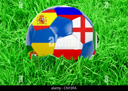 Soccer ball on grass field background. Ball filled with euro 2012 countries flags colors. - Stock Photo