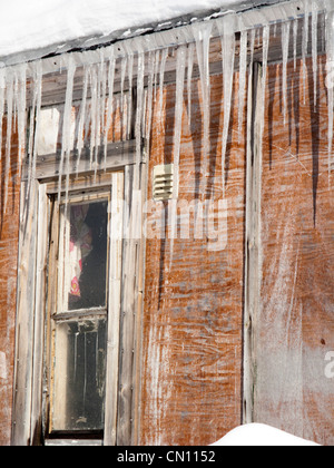 Icicles hanging down from the roof of a house - Stock Photo