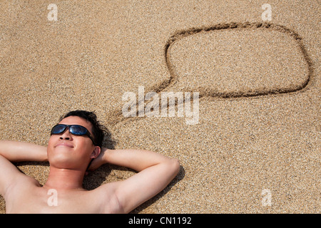 smiling young man lying on the beach and dialog symbol - Stock Photo