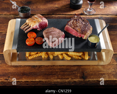 Rack of lamb rib eye and fillet steak on a hot lava stone with chips underneath - Stock Photo
