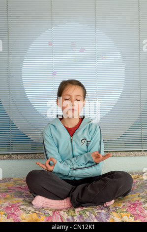 Young girl practising meditation in her room - Stock Photo