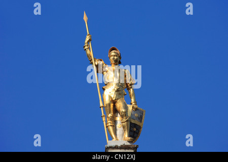 Golden statue of a medieval herald on top of a house at the Market Place in Antwerp, Belgium - Stock Photo