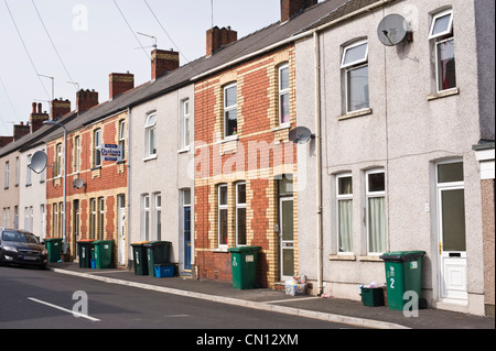 Street of terraced houses in Newport South Wales UK with wheelie bins outside - Stock Photo