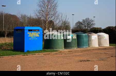 A line of recycling collection containers by a car park in the village of Mulbarton, Norfolk, England, United Kingdom. - Stock Photo