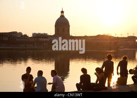 People sit on the banks of La Garonne, as the sun sets close to Dome de la Grave, Toulouse, France - Stock Photo