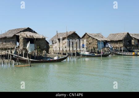 Bamboo huts and boats along a waterway. Irrawaddy delta. Myanmar. - Stock Photo