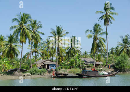 Bamboo huts boats and coconut trees along a waterway. Irrawaddy delta. Myanmar. - Stock Photo