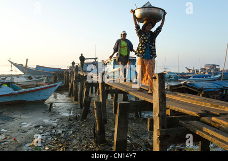Women at a wooden jetty in Labutta harbour. Irrawaddy delta. Myanmar. - Stock Photo