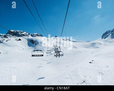 Chairlift with skiers at Les Blanchettes above La Plagne in the French alps - Stock Photo