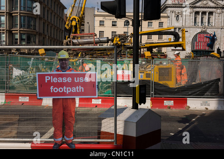 Real construction workers in the background and a scaled human workman figure who warns pedestrians to stay on established - Stock Photo