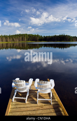 Two White Adirondack Chairs On A Lawn Overlooking The