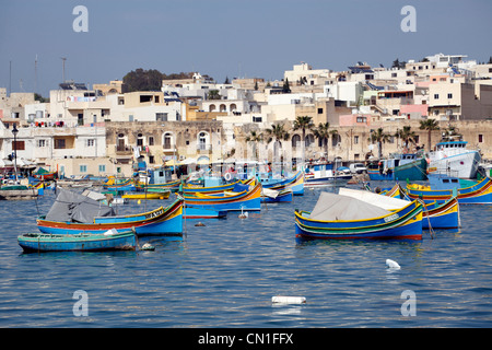 Traditional Maltese fishing boats known as dghajsa in the harbour at Marsaxlokk, Malta - Stock Photo