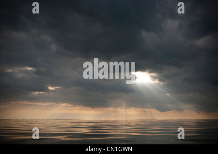 Sunlight Filtering Dramatic Gray Clouds Over Water - Stock Photo