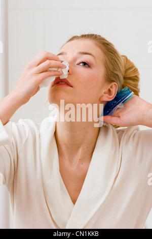 Woman suffering from nosebleeding - Stock Photo