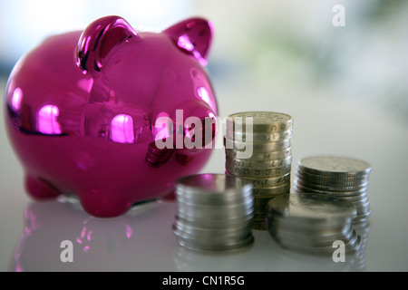 Pink piggy bank and piles of money - Stock Photo