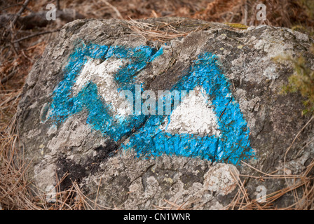 Hiking signs, arrow and triangle, painted in blue and white on a rock - Stock Photo