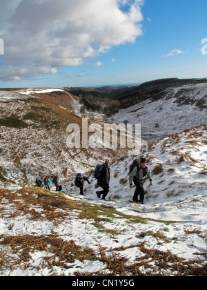 Waking group climbing in snow out of Thorodale in the North Yorks Moors National Park - Stock Photo