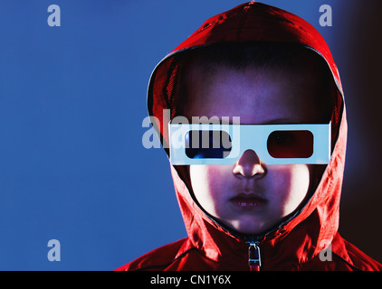Young boy wearing 3d glasses and red hooded top - Stock Photo