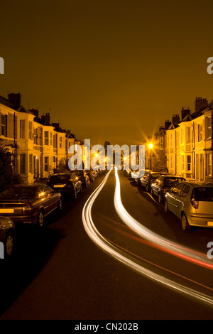 Residential street at night time with tail light of traffic - Stock Photo