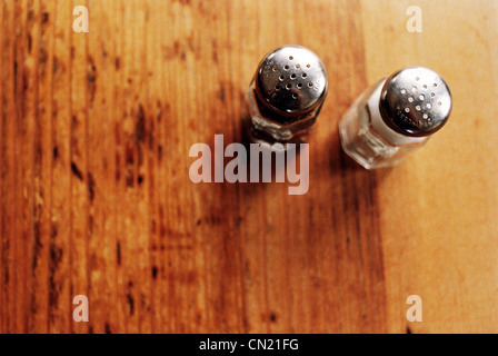 Salt and pepper pots on wooden table - Stock Photo