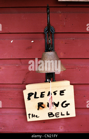 Metal bell and sign saying please ring the bell - Stock Photo