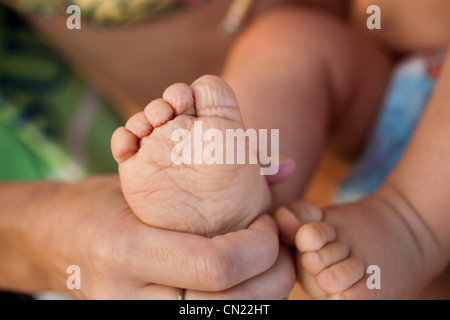 Mother touching child's foot, close up - Stock Photo