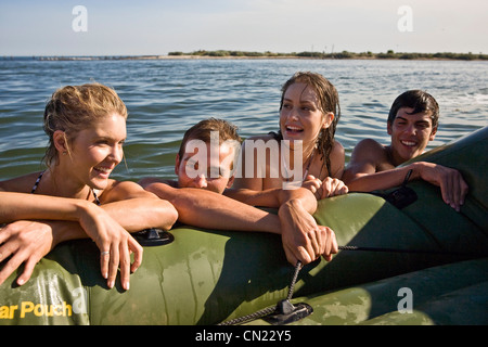 Two Smiling Young Couples in Water Resting on Side of Dinghy - Stock Photo