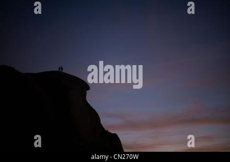 Rock climbers at sunset, Joshua Tree national park, California, USA - Stock Photo