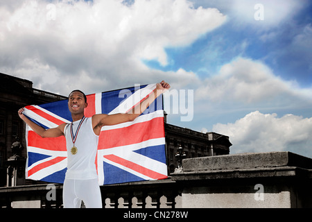 Olympic gold medal winner with Union Jack - Stock Photo