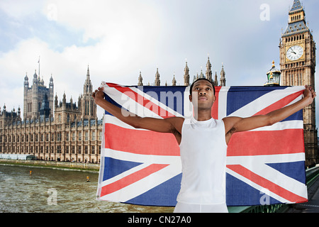 Olympic competitor with Union Jack in front of Houses of Parliament, London, England - Stock Photo