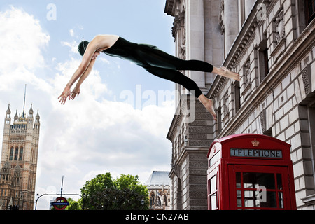 Swimmer diving from red telephone box, London, England - Stock Photo