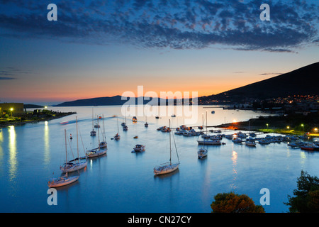 Sailboats docking by old town Trogir in Dalmatia at sunset. - Stock Photo