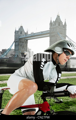 Cyclist with Tower Bridge in background, London, England - Stock Photo