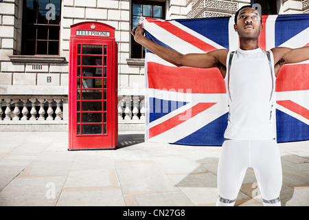 Olympic competitor with Union Jack and red telephone box in background - Stock Photo