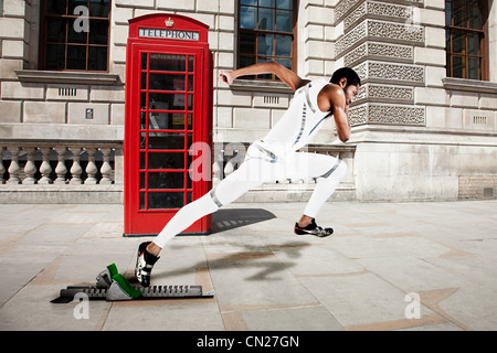 Olympic sprinter on starting line with red telephone box in background - Stock Photo