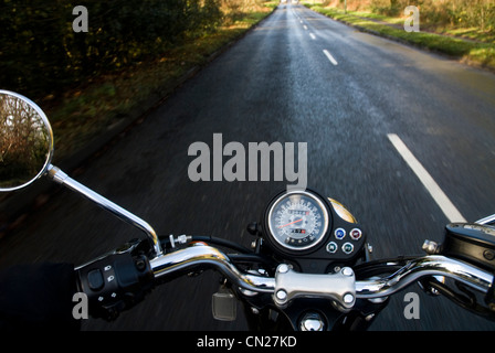 Motorbike on empty rural road - Stock Photo