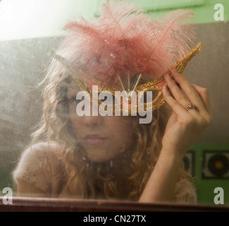 Teenage girl wearing masquerade mask in front of mirror - Stock Photo