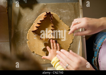 Mother and daughter cutting dough with cookie cutters - Stock Photo