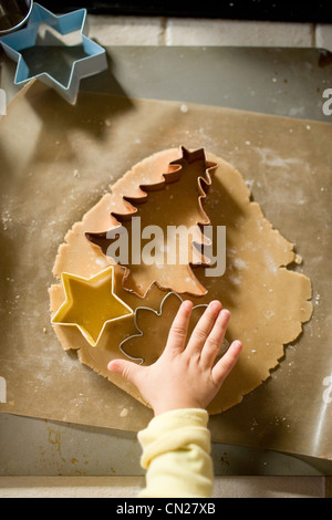 Girl cutting dough with cookie cutters - Stock Photo