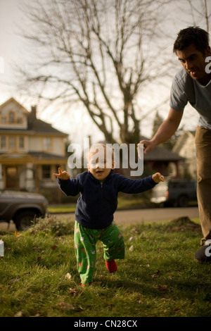 Father with son taking first steps - Stock Photo