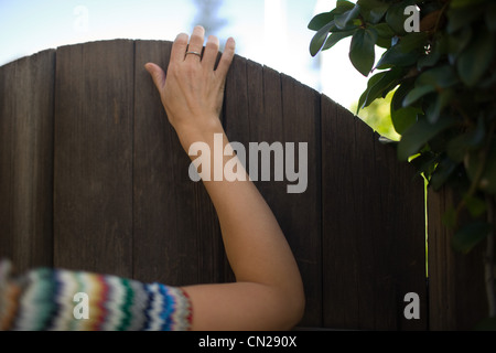 Woman's hand on gate - Stock Photo