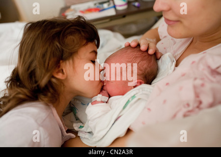 Mother with newborn baby boy and daughter in hospital bed - Stock Photo