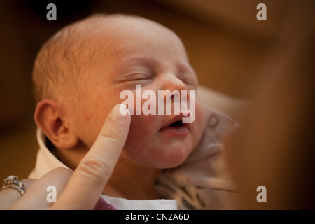 Mother touching newborn baby boy's face with finger - Stock Photo