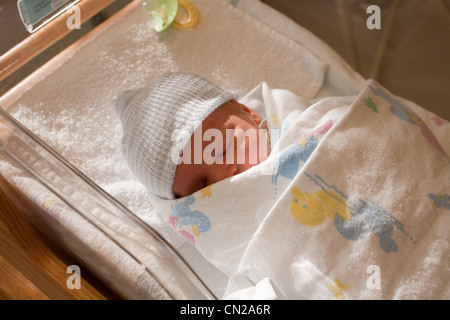 Newborn baby boy in hospital crib - Stock Photo