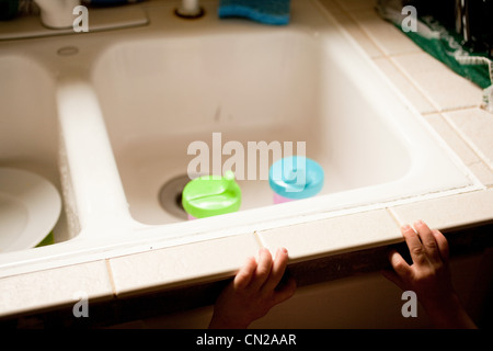 Child reaching towards kitchen sink with beakers - Stock Photo