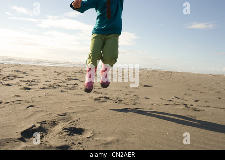 Young girl jumping on sandy beach - Stock Photo