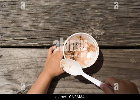 Young girl eating bowl of ice cream with spoon
