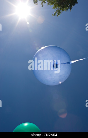 Blue balloon against blue sky - Stock Photo