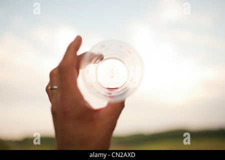 Woman's hand holding empty drinking glass - Stock Photo